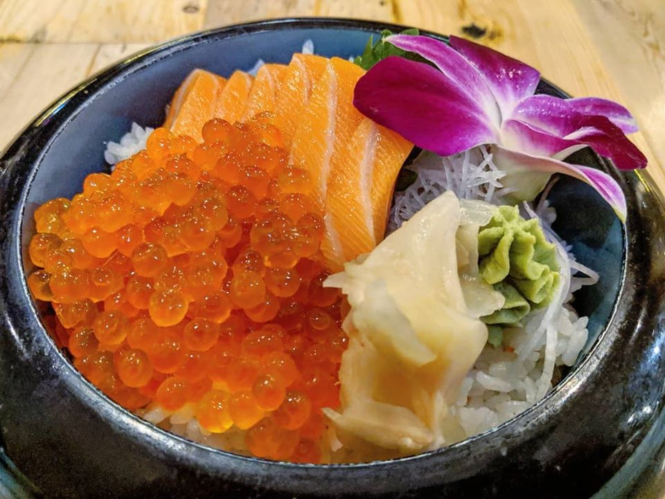 A bowl of white rice topped with slices of raw salmon, orange balls of salmon roe, wasabi, pickled ginger, and a decorative orchid