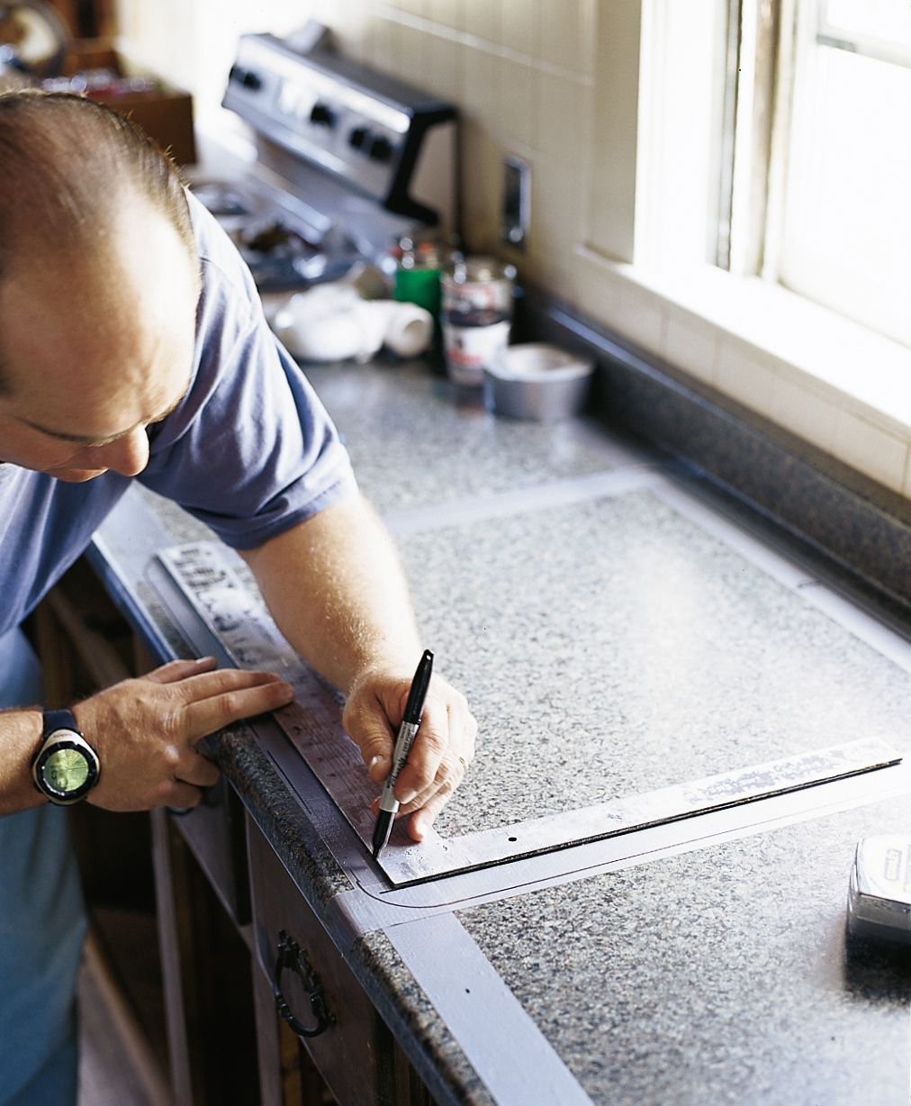 Person marking a counter with a sharpie to prepare for new kitchen sink installation.