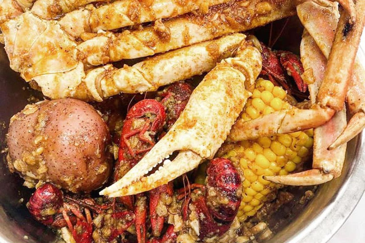 a silver metal bowl full of vietnamese-style crawfish, crab legs, corn and potatoes