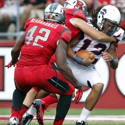 Howard quarterback Jamie Cunningham (12) is sacked by Rutgers linebacker Kevin Snyder  as linebacker Steve Beauharnais (42) helps out during the first half of an NCAA college football game at Highpoint Solutions stadium Saturday, Sept. 8, 2012, in Piscataway, N.J.