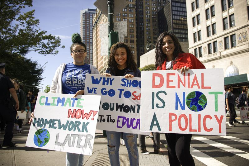 """Three young woman hold protest signs at the Global Climate Strike in New York City. The signs read, """"Climate now! Homework later,"""" and, """"Denial is not a policy."""""""