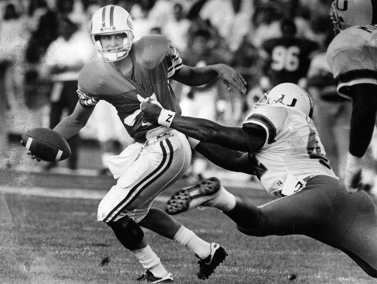 BYU quarterback Ty Detmer escapes from Miami's Shane Curry to throw the first Cougar touchdown against Miami in 1990.