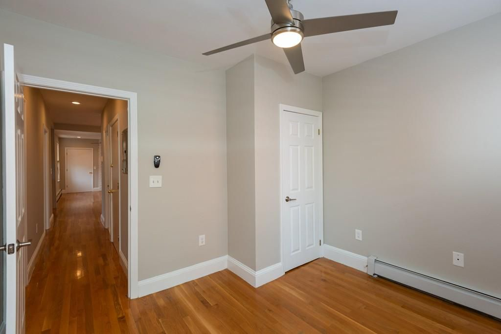 An empty bedroom with a ceiling fan, and the room is off a long hallway.