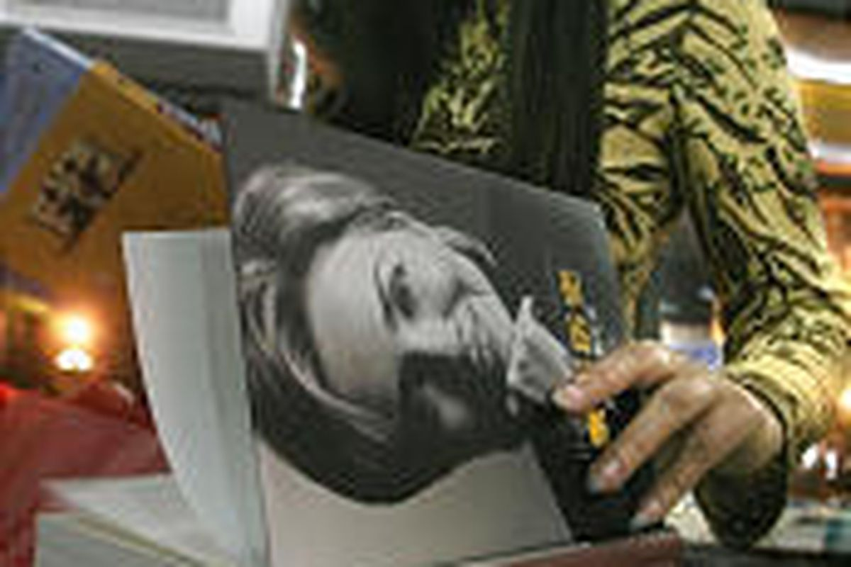 """A Chinese woman looks at a copy of Hillary Clinton's memoir, """"Living History,"""" at a bookstore in Beijing."""