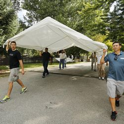 Latter-day Saint volunteers Jason Carter and Dave Watkins set up a tent as they help Catholics set up for the Carmelite Fair at the monastery in Holladay Tuesday, Sept. 16, 2014.