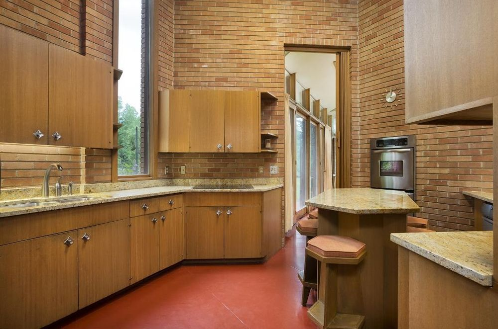 A midcentury modern kitchen with exposed tank brick, granite countertops, wooden cabinetry, and high ceilings.