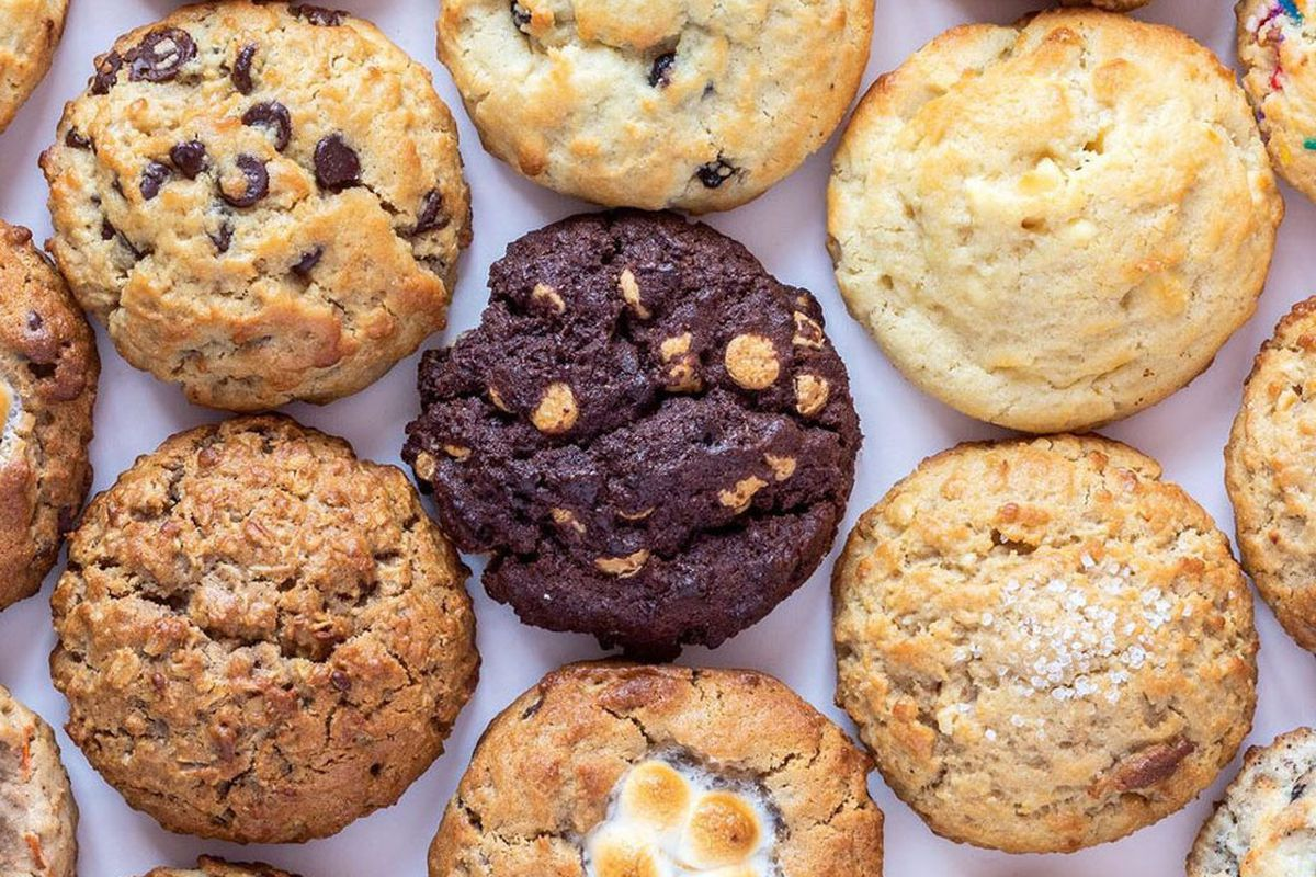 A close-up shot of a variety of cookies, including chocolate chip and oatmeal, laid out on a cookie sheet