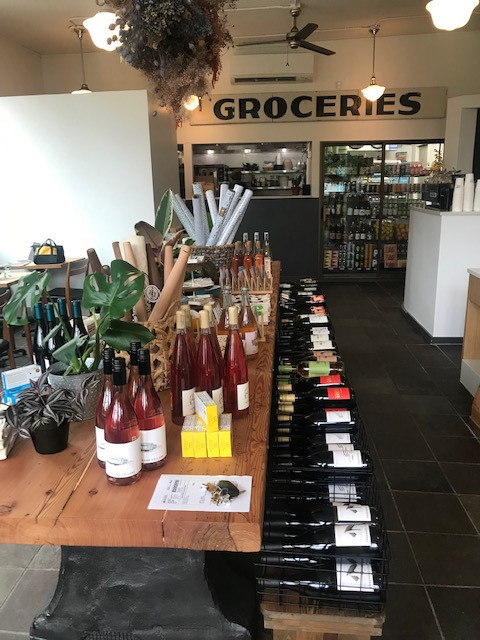 """A selection of wine bottles on a table with a large vintage sign that says """"Groceries"""" in the background."""