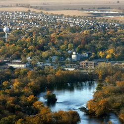 FILE - This Oct. 2010 aerial file photo shows the Fox River as it flows into downtown Oswego, Ill., in Kendall County, with subdivisions and farmland to the southeast.  The nation's No. 1 fastest-growing county from 2000 to 2010, Kendall was part of an exurban wave in the heady 2000s that more than doubled its population. But Census estimates as of July 2011 highlight a shift in population trends, following an extended housing bust and renewed spike in oil prices: outlying suburbs are now seeing their growth fizzle to historic lows, halting American city dwellers' decades-long exodus to sprawling homes in distant towns.