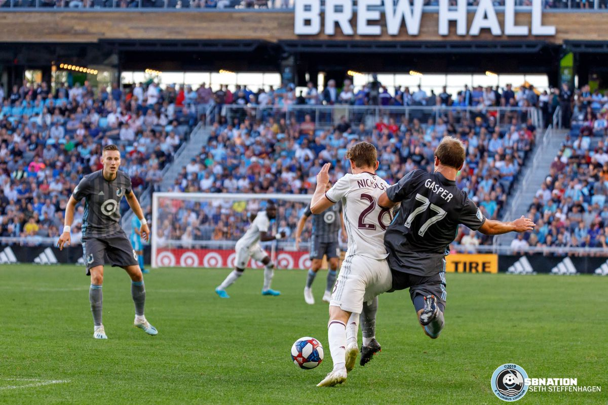 August 14, 2019 - Saint Paul, Minnesota, United States - Minnesota United defender Chase Gasper (77) goes in for a slide tackle on Colorado Rapids midfielder Sam Nicholson (28)during the match at Allianz Field.
