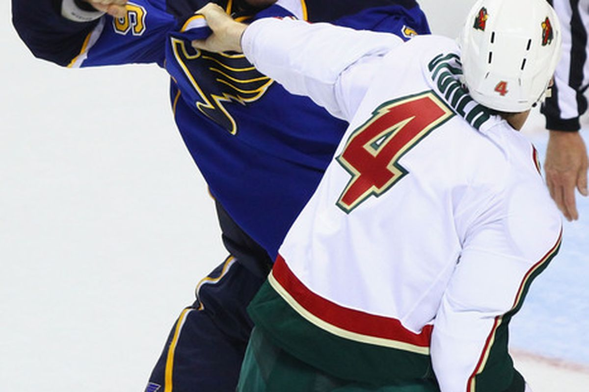 ST. LOUIS - SEPTEMBER 24: B.J. Crombeen #26 of the St. Louis Blues fights Clayton Stoner #4 of the Minnesota Wild during a pre-season game at the Scottrade Center on September 24 2010 in St. Louis Missouri.  (Photo by Dilip Vishwanat/Getty Images)