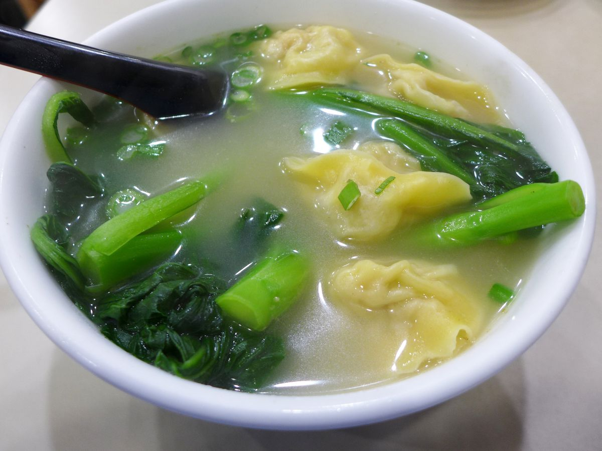 A white bowl with a soup in it from within which yellow dumplings are seen peeking out along with leafy greens.