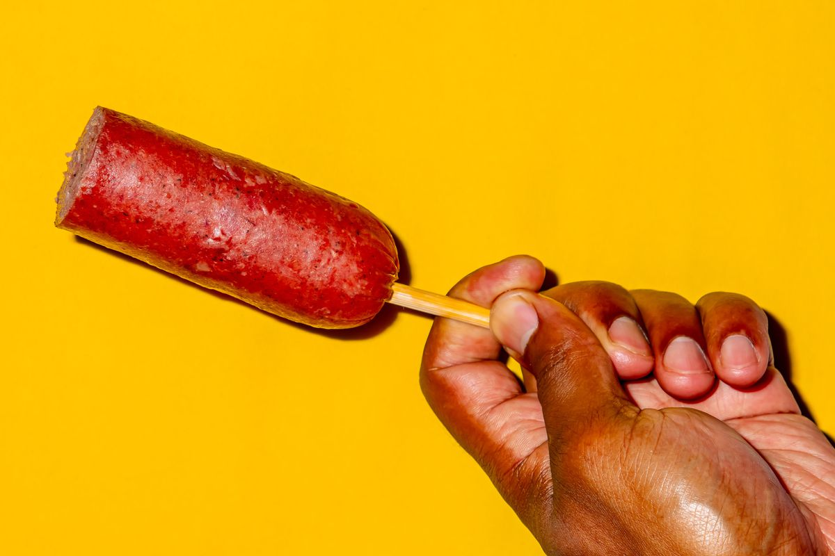 A hand holding a Dutch bologna on a stick against a yellow background