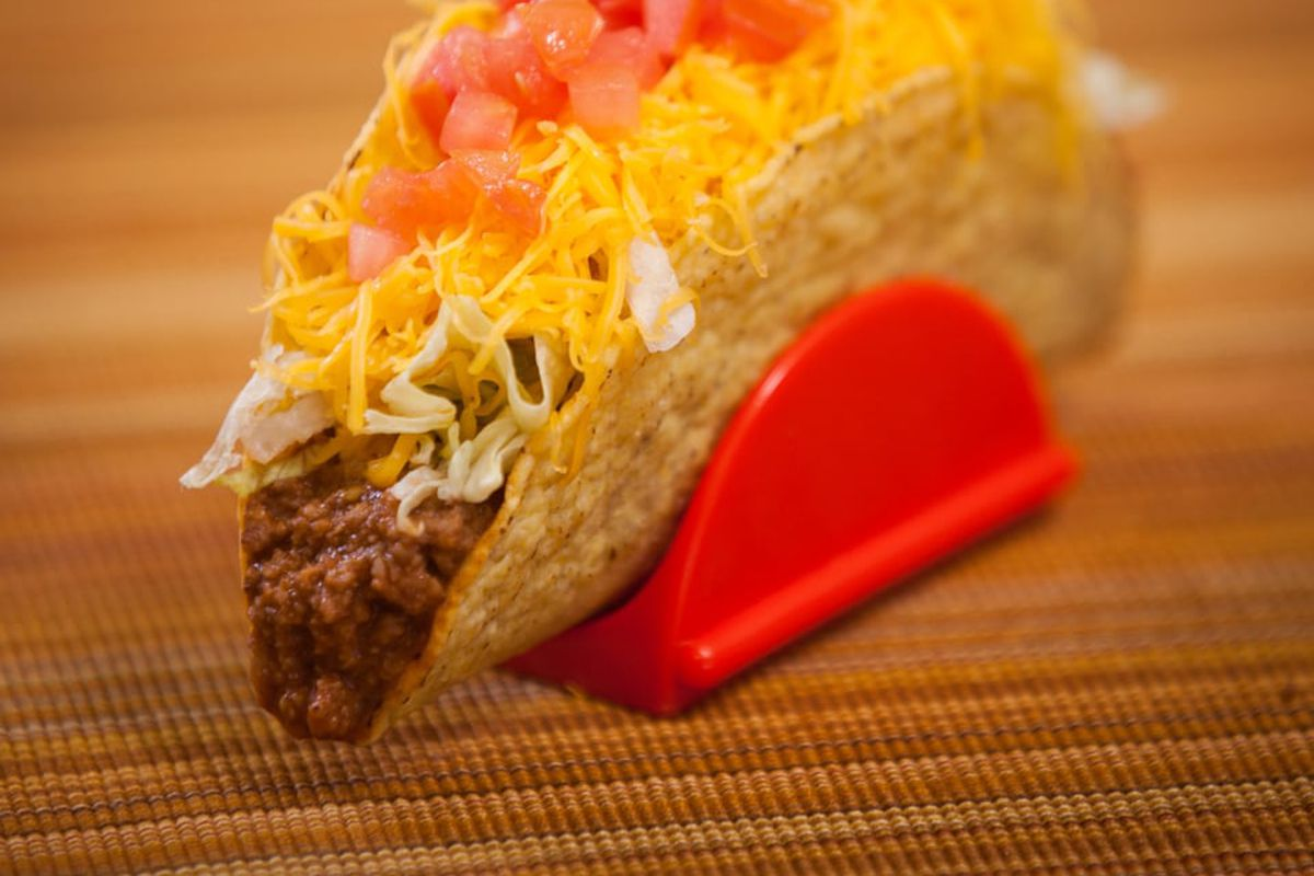 A hard shelled taco sits in a tray, loaded with beef.