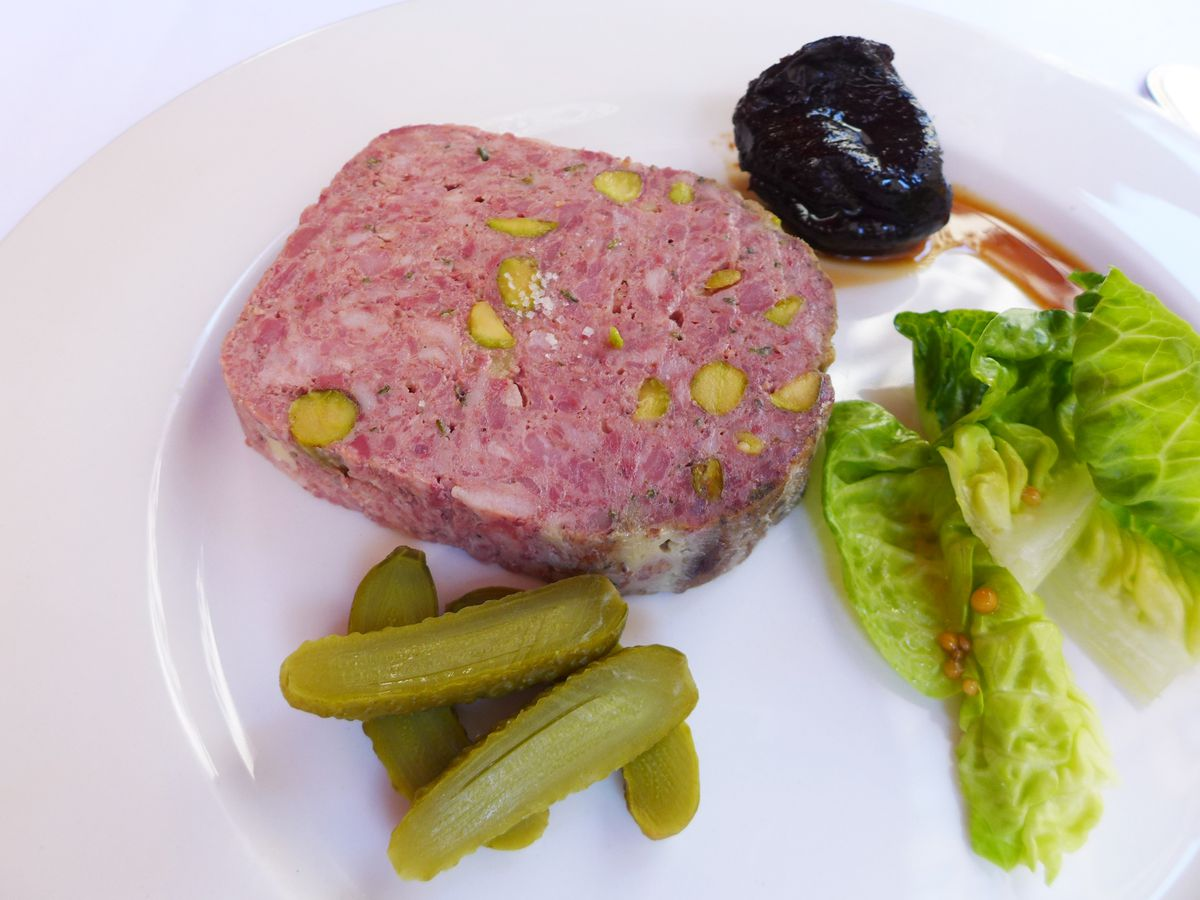 Slab of pate, cornichons, baby lettuces, and stewed prune.