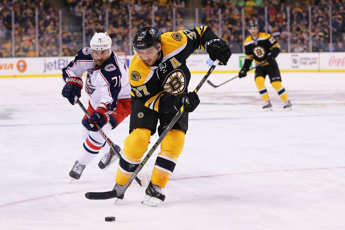 Columbus Blue Jackets v Boston Bruins, Patrice Bergeron moves the puck up ice, tailed by Nick Foligno.