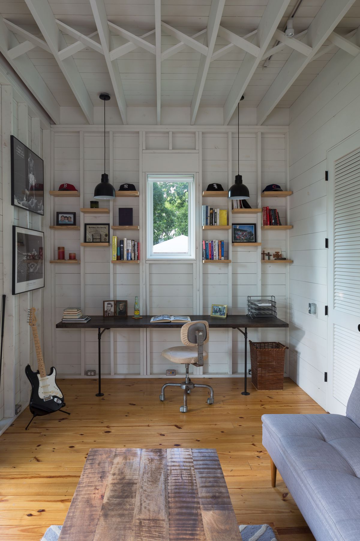 small study/lounge area in cottage-style room with desk, couch, coffee table, guitar