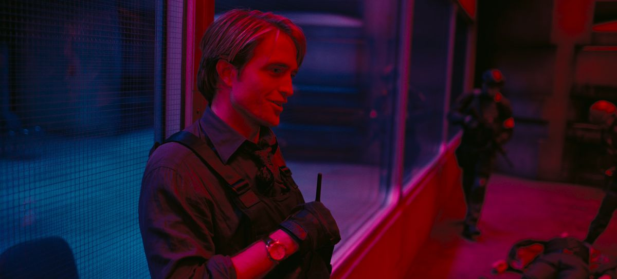 Robert Pattinson wearing a bullet-proof vest as Neil in Tenet washed with red and blue light