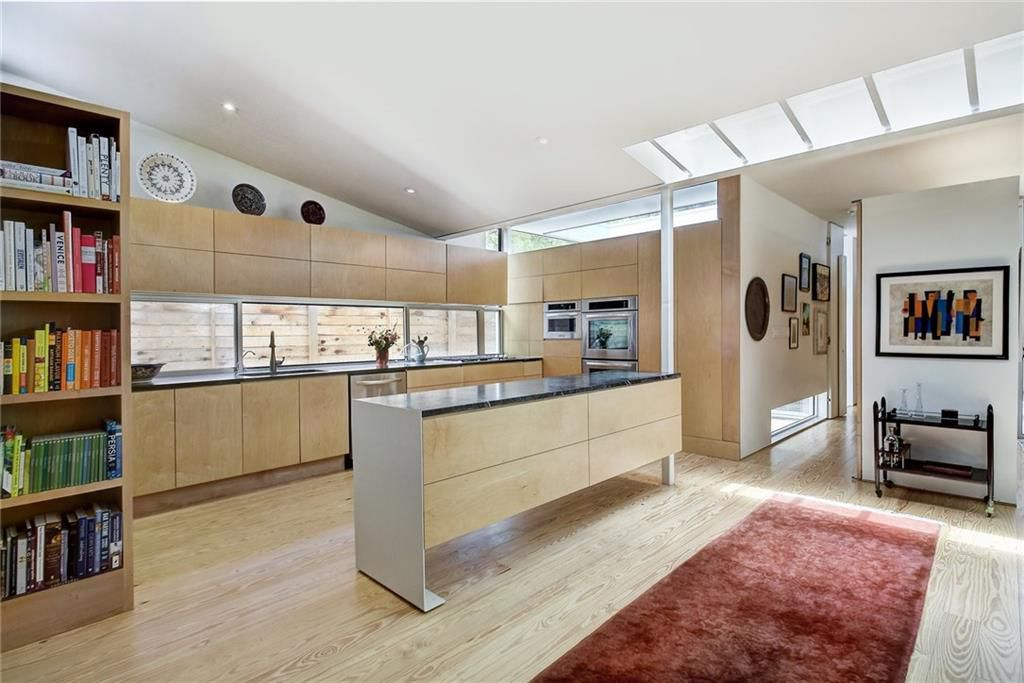 An open-plan modern kitchen with a row of upper and lower shelves against the back wall with a long strip of a window along the wall above the counter and sink. It has an island with the same wood on the side and a bookshelf to the left. The wood shelves extend to the side wall, where ther is an inset double oven and microwave, all stainless steel. There's a runner rug in front and a hallway leading away from the room.