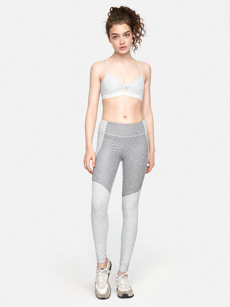 A model in grey leggings and a sports bra
