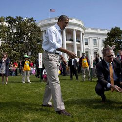 President Barack Obama goes to help a little egg roller on the South Lawn of the White House in Washington, Monday, April 9, 2012, during the annual White House Easter Egg Roll.