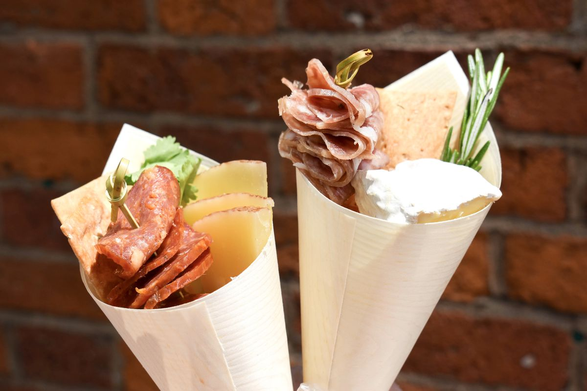 Two beige paper cones filled with meat, cheese, and sprigs of fresh herbs.