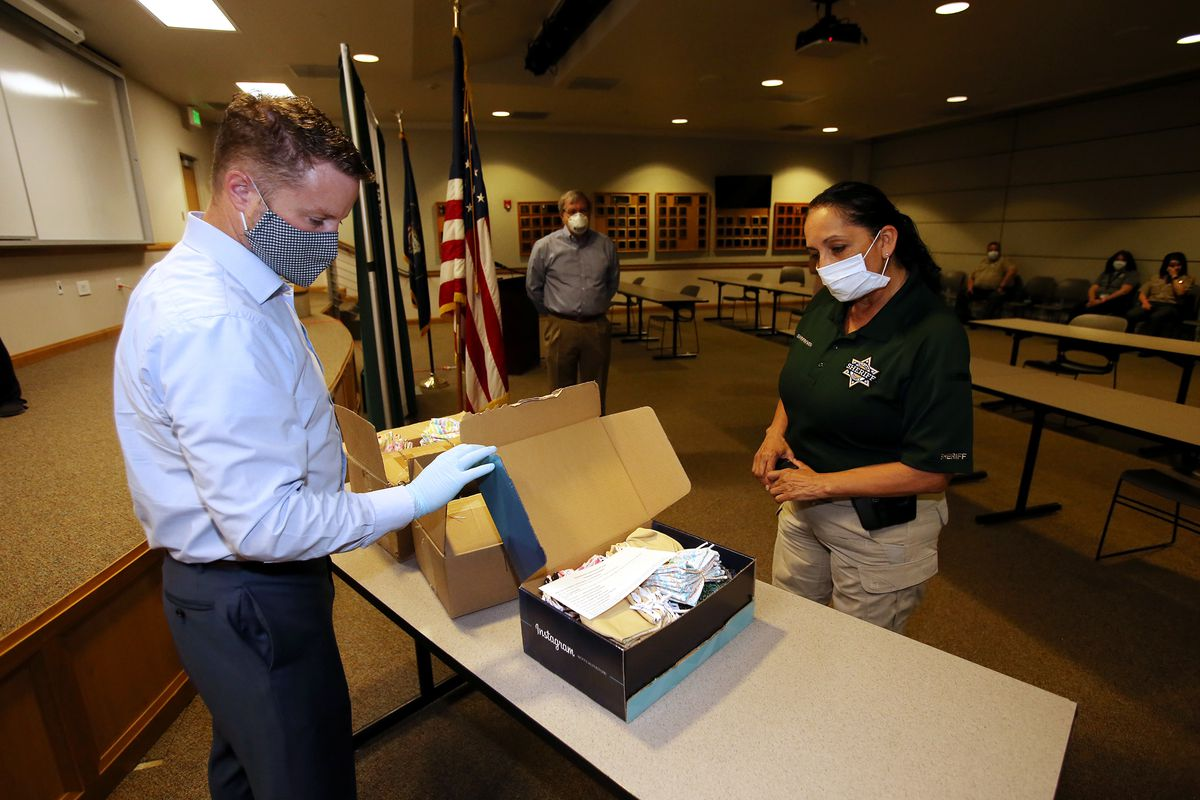 David Kelly, chairman the Pioneer Park Coalition, shows Salt Lake County Sheriff Rosie Rivera some of the face masks being donated to inmates at the Salt Lake County Jail during an event at the Salt Lake County Sheriff's Office in South Salt Lake on Monday, May 11, 2020. The masks were made by members of the Utah's Vietnamese community to help slow the spread of COVID-19.