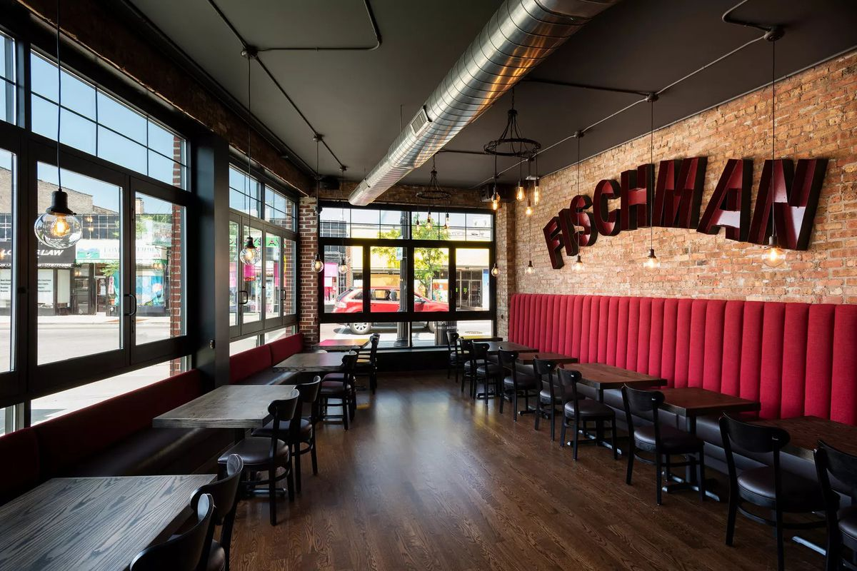 """A large open dining room with a red sign that reads, """"Fischman."""""""