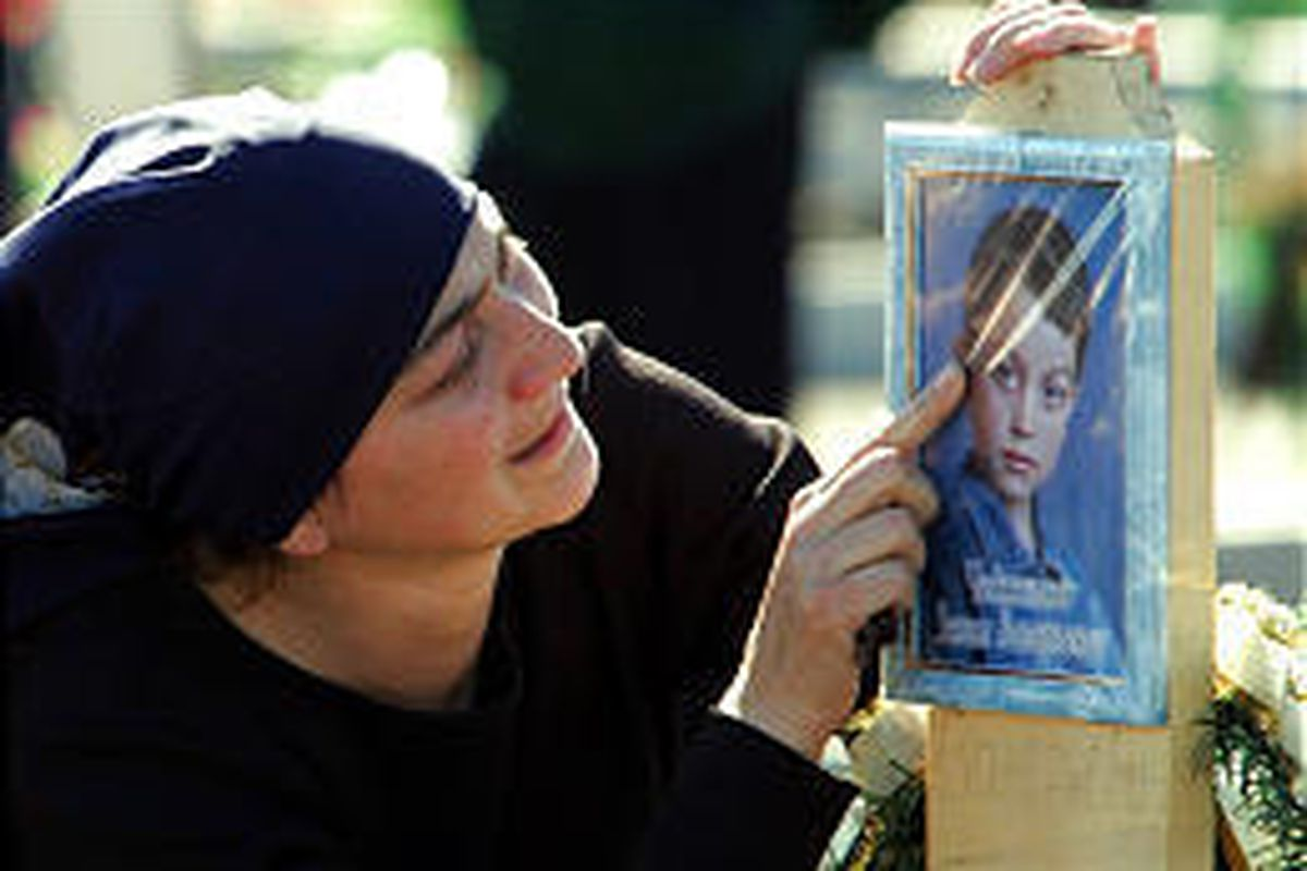 A woman touches a portrait of school massacre victim Zelim Chedzhemov, 9, at a cemetery in Beslan, North Ossetia, Monday.