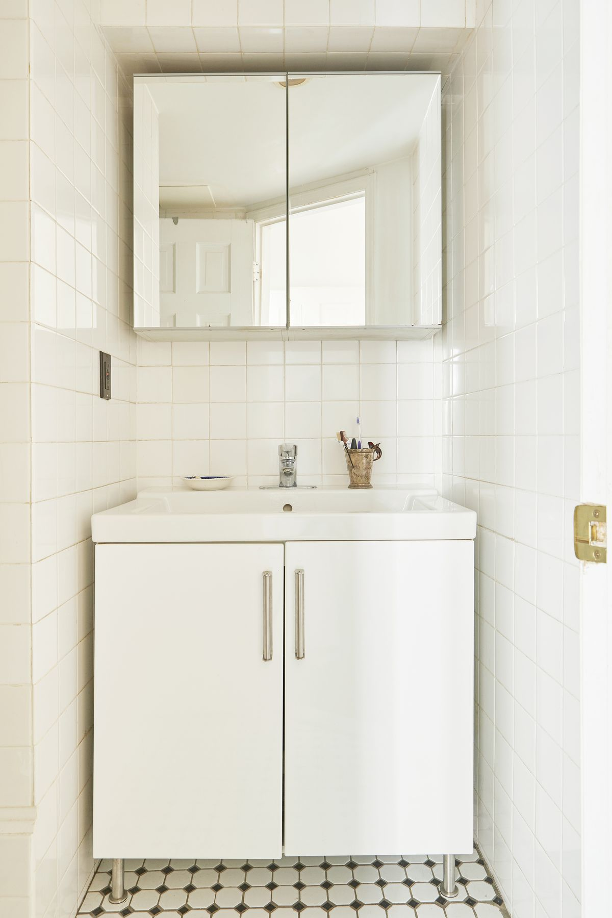 A mirrored bathroom cabinet hangs over a white sink.