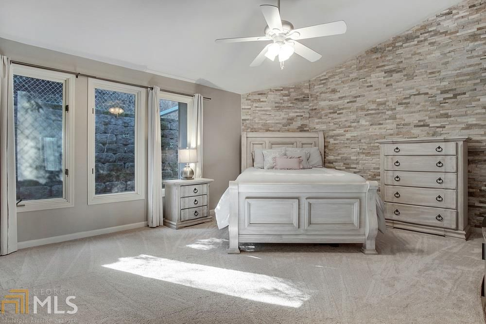 Bedroom with bed, nightstand, dresser and stacked stone wall.