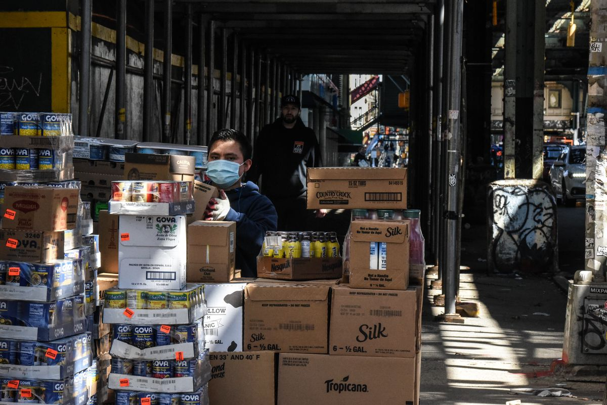 A worker wearing a face mask receives a food delivery at a grocery store in the Bushwick neighborhood of Brooklyn