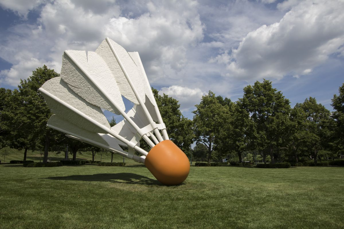 A giant sculpture of a shuttlecock on grass at the Donald J. Hall Sculpture Park in Kansas City. There are trees in the background.