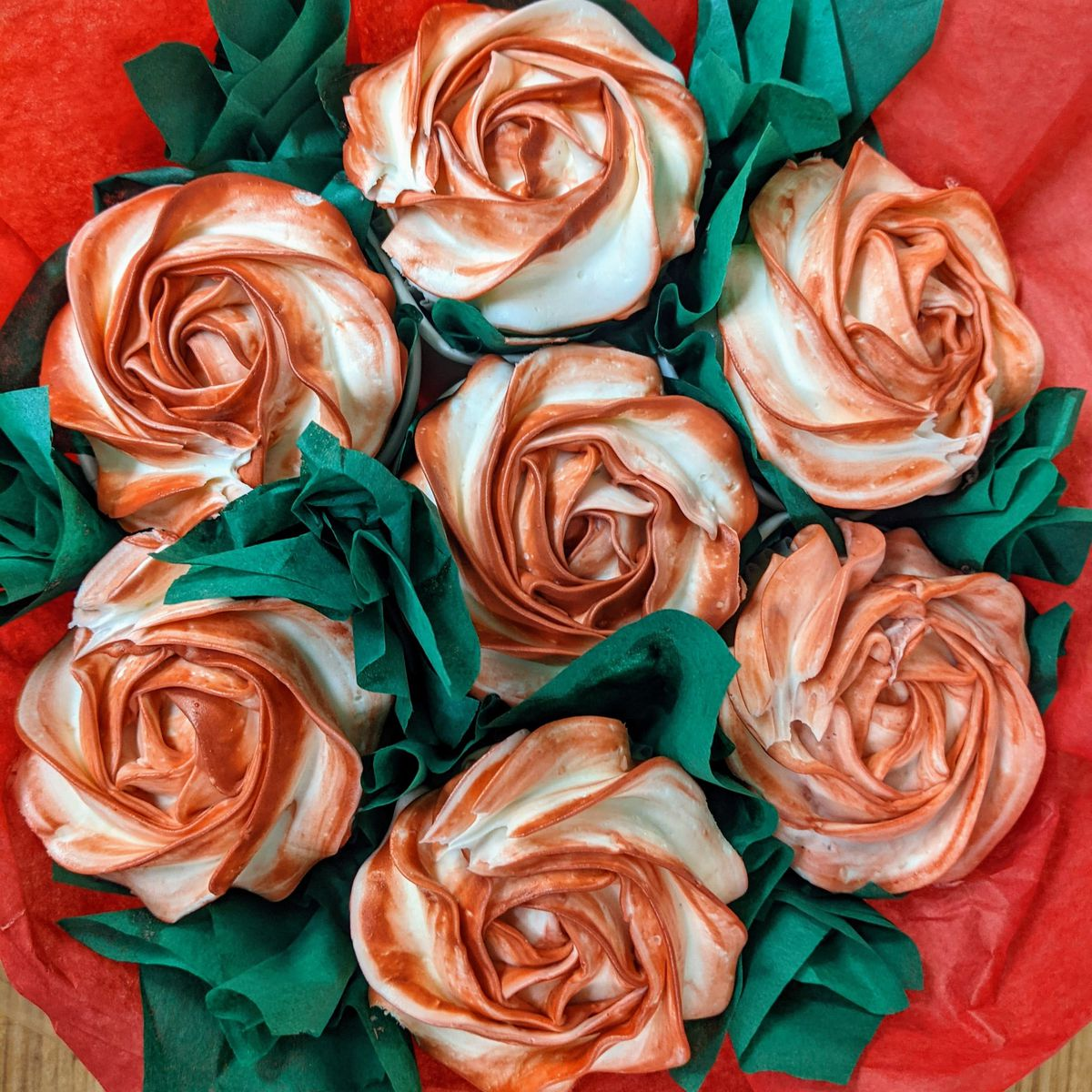 Seven cupcakes in a circle decorated to look like roses.