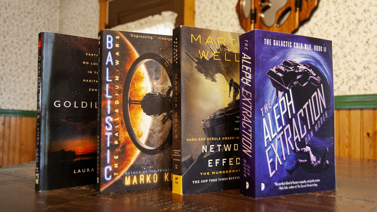 Four science fiction books upright on a book shop counter