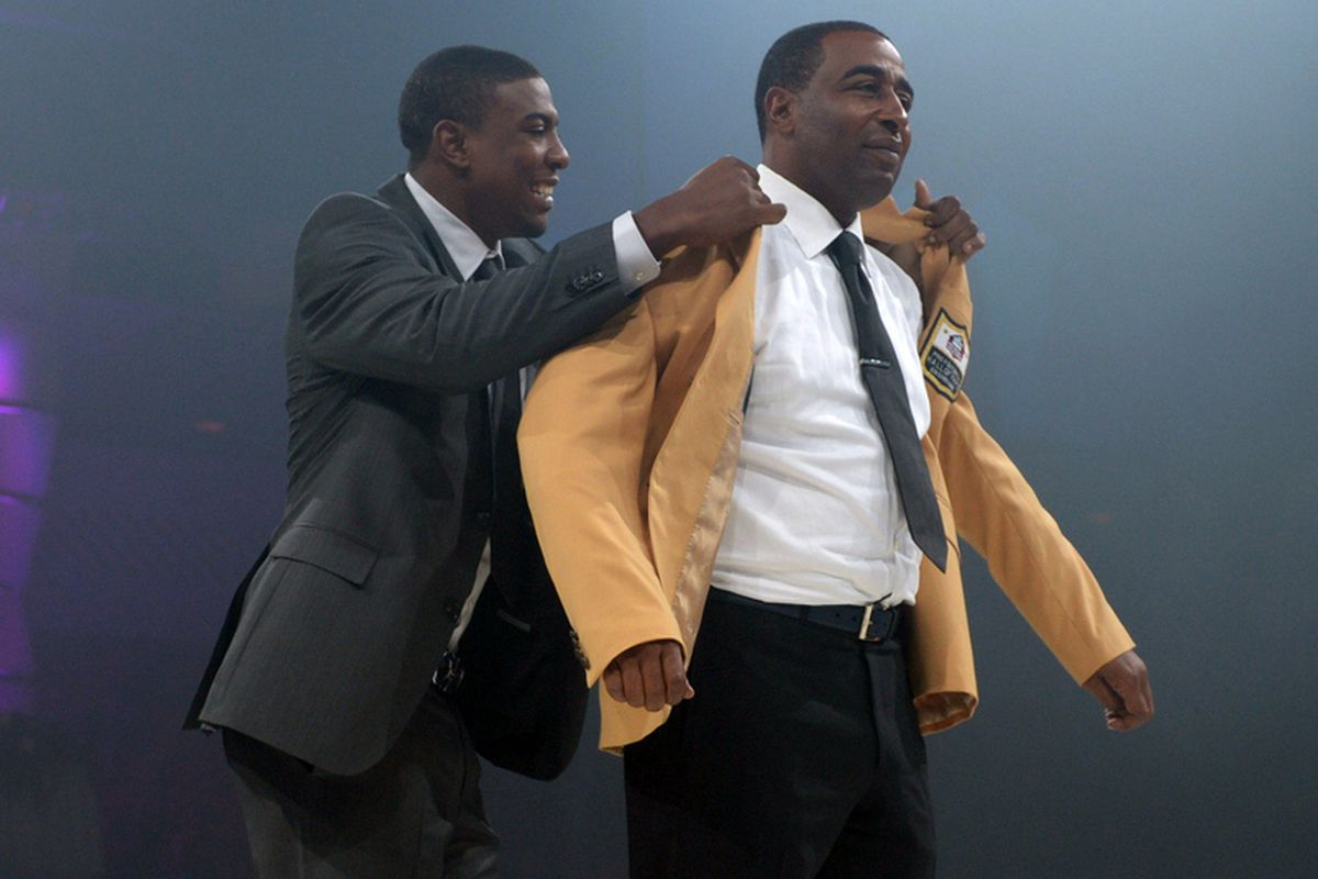 Aug 2, 2013; Canton, OH, USA; Duron Carter (left) presents his father Cris Carter with the gold jacket at the 2013 Pro Football Hall of Fame Enshrinees Gold Jacket Dinner at the Canton Memorial Civic Center.