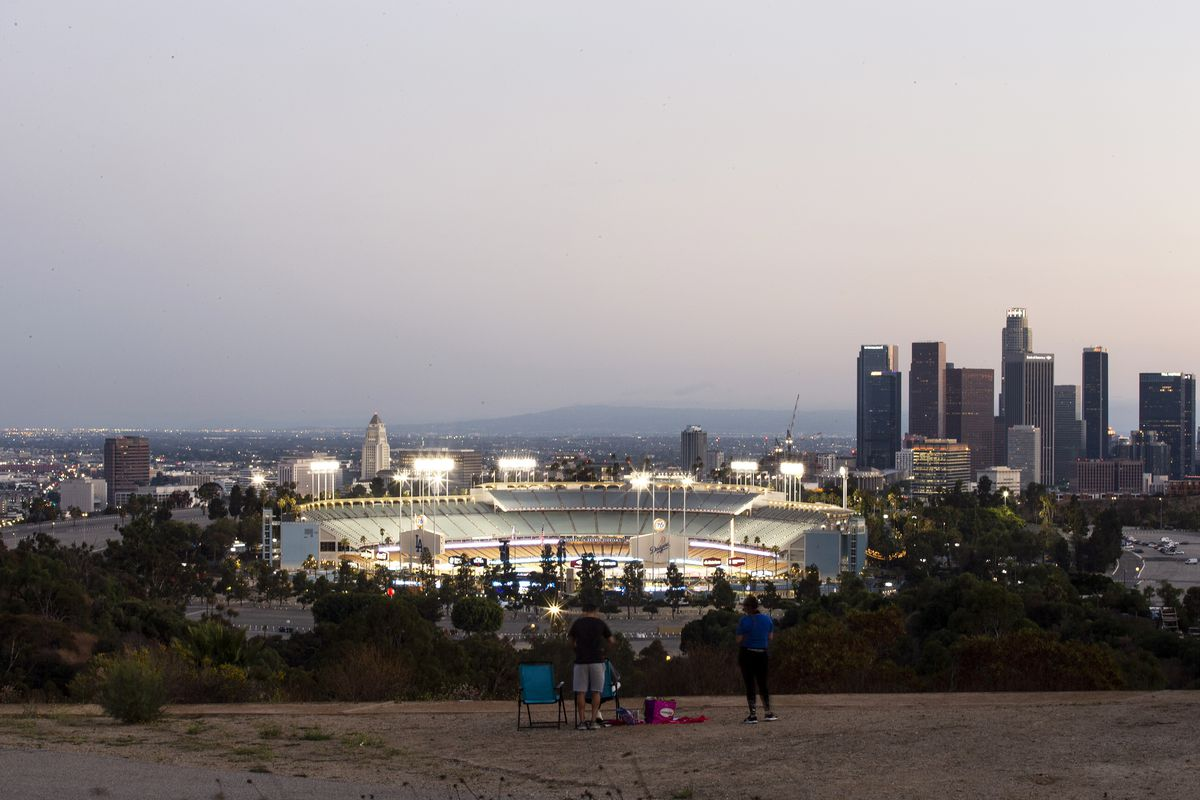 A family sits on chairs in a parking lot above the lights of Dodger Stadium, where teams are playing but no fans are in the stand, with the skyline of downtown LA behind.