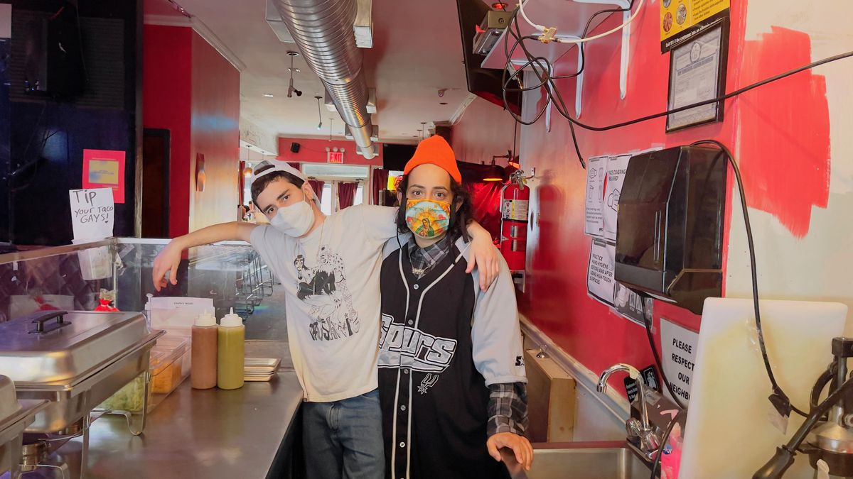 Two people in a kitchen wearing masks and looking at the camera