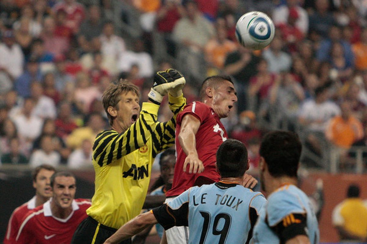 HOUSTON - JULY 28:  Edwin van der Sar #1 and Federico Macheda #27 of Manchester United jump to defend the ball during the MLS All Star Game at Reliant Stadium on July 28 2010 in Houston Texas.  (Photo by Bob Levey/Getty Images)