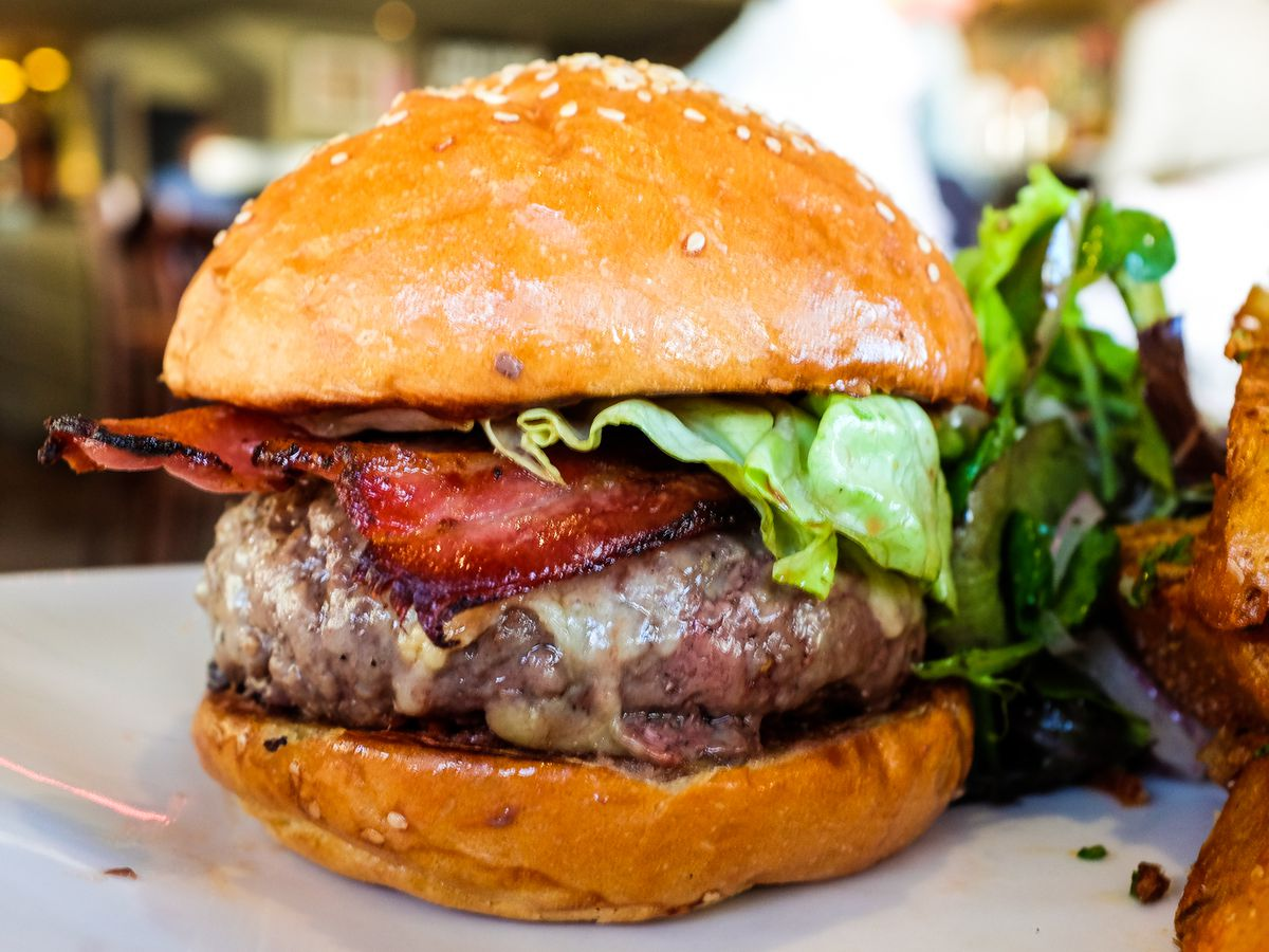 Closeup on a burger featuring a thick patty, bacon, lettuce, and cheese, with thick fries on the edge of the frame