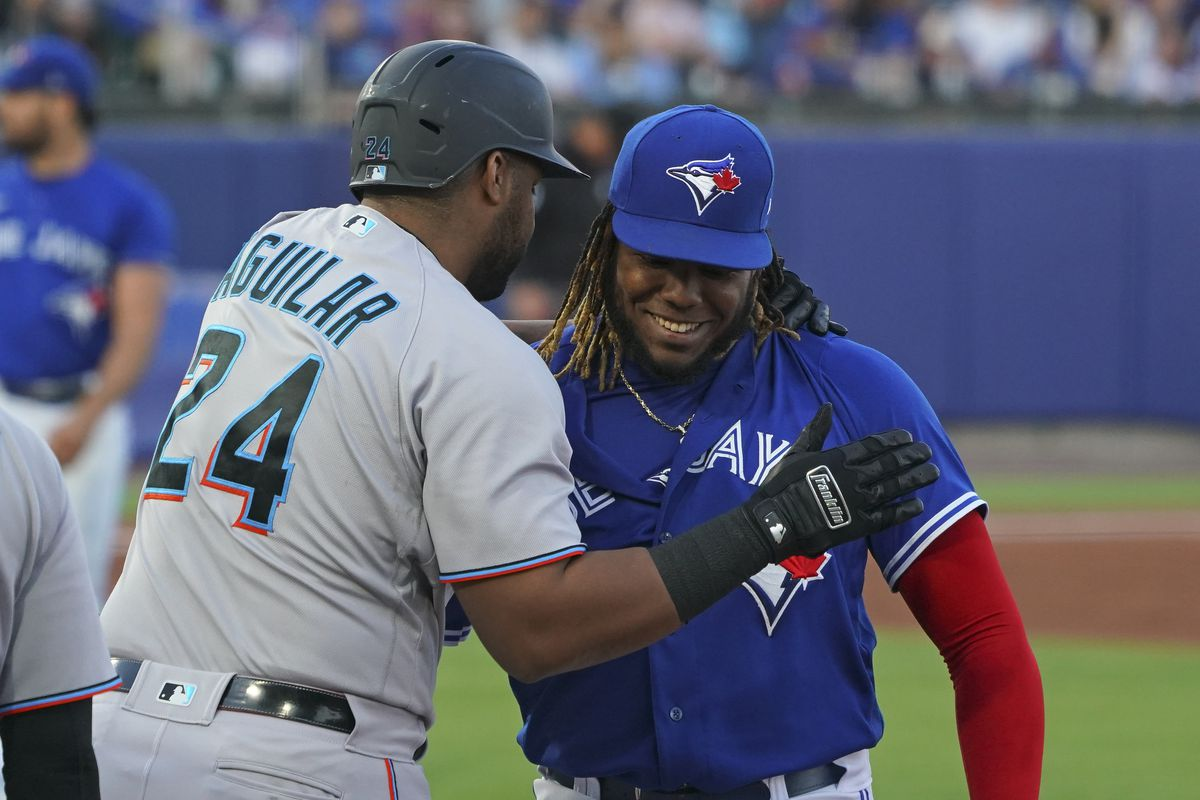 Jesus Aguilar #24 of the Miami Marlins and Vladimir Guerrero Jr. #27 of the Toronto Blue Jays during the game at Sahlen Field