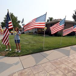Cora McIllece and Lena McIllece, friends and neighbors, put up flags around house belonging to the father of U.S. Marine Staff Sgt. Darin Taylor Hoover Jr. in Sandy on Friday, Aug. 27, 2021. Hoover Jr. was killed in the suicide bombing at the Kabul Airport in Afghanistan.