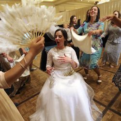Female guests fan Chaya Zippel during her and Rabbi Mendy Cohen's traditional Chabad Lubavitch Jewish wedding at the Grand America Hotel in Salt Lake City on Monday, Sept. 12, 2016. Men and women celebrate separately.