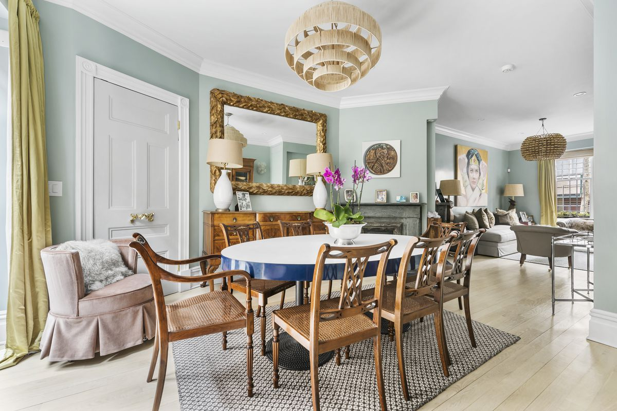 A dining area with a round table, light blue walls, crown moldings, and hardwood floors.