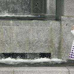 Tatiana Herrera, 4, of Colombia, enjoys playing beside the waterfall at the LDS Conference Center before the Saturday morning session of general conference.