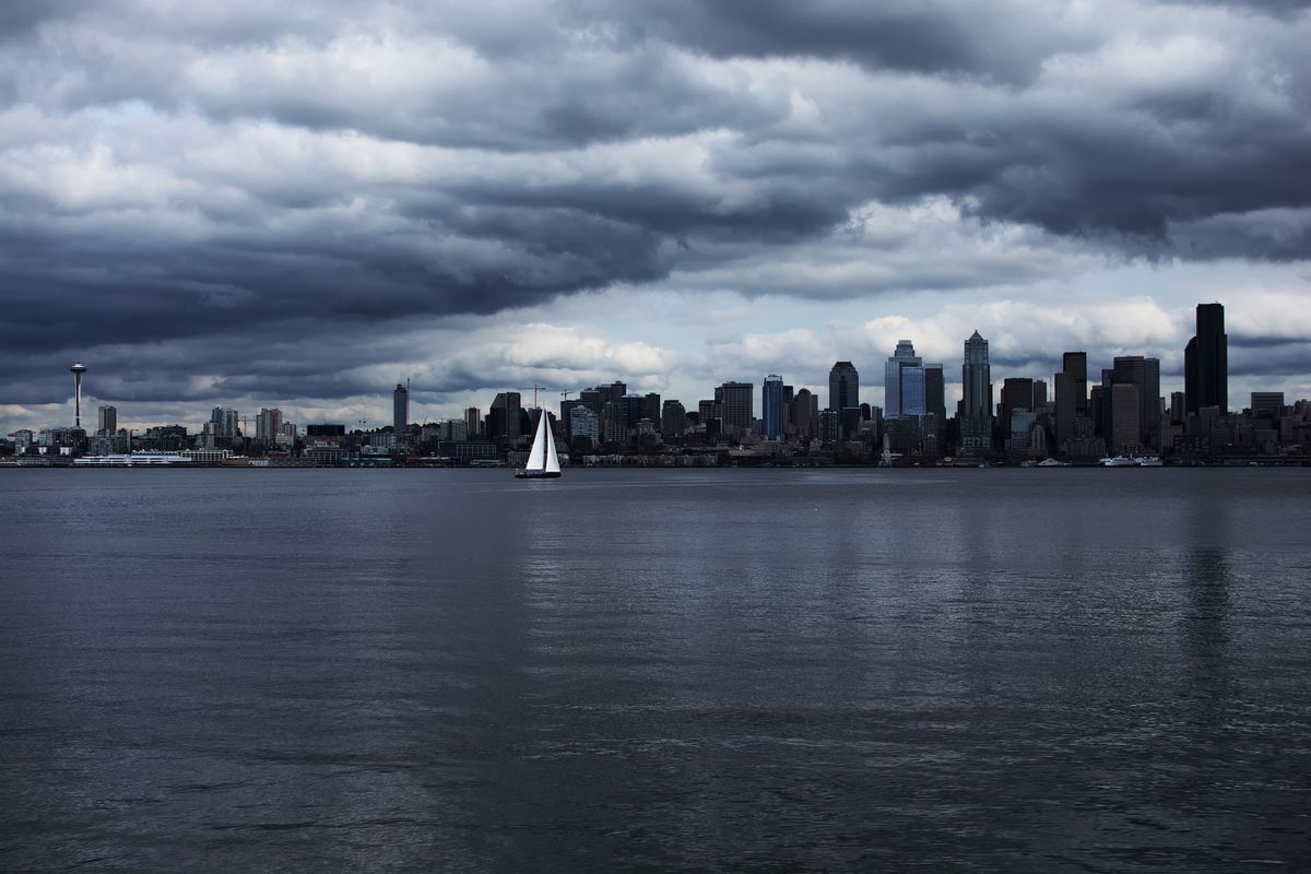 The Downtown Seattle skyline with heavy cloud cover is viewed from across Elliott Bay. A sailboat is on the water toward the center.