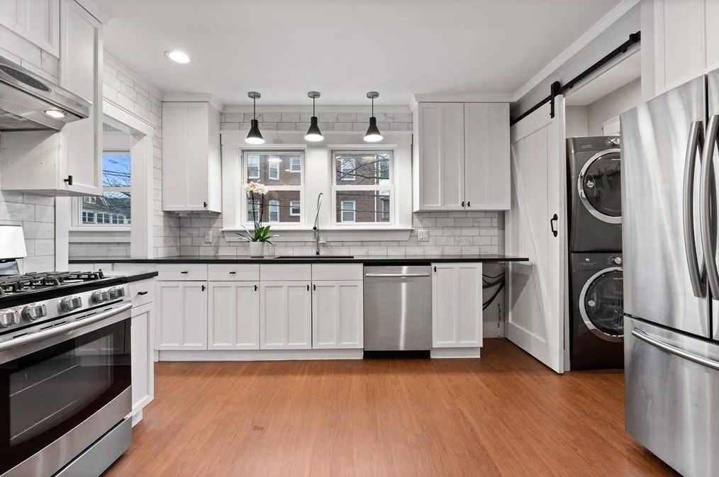 A modern kitchen with a stacked washer-dryer.