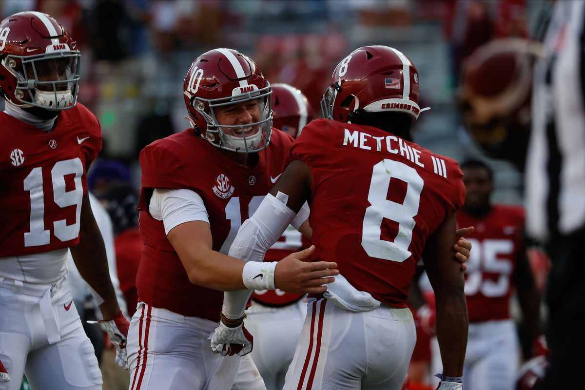 John Metchie III and Mac Jones of the Alabama Crimson Tide celebrate a touchdown run against the Texas A&M Aggies on October 3, 2020 at Bryant-Denny Stadium in Tuscaloosa, Alabama.