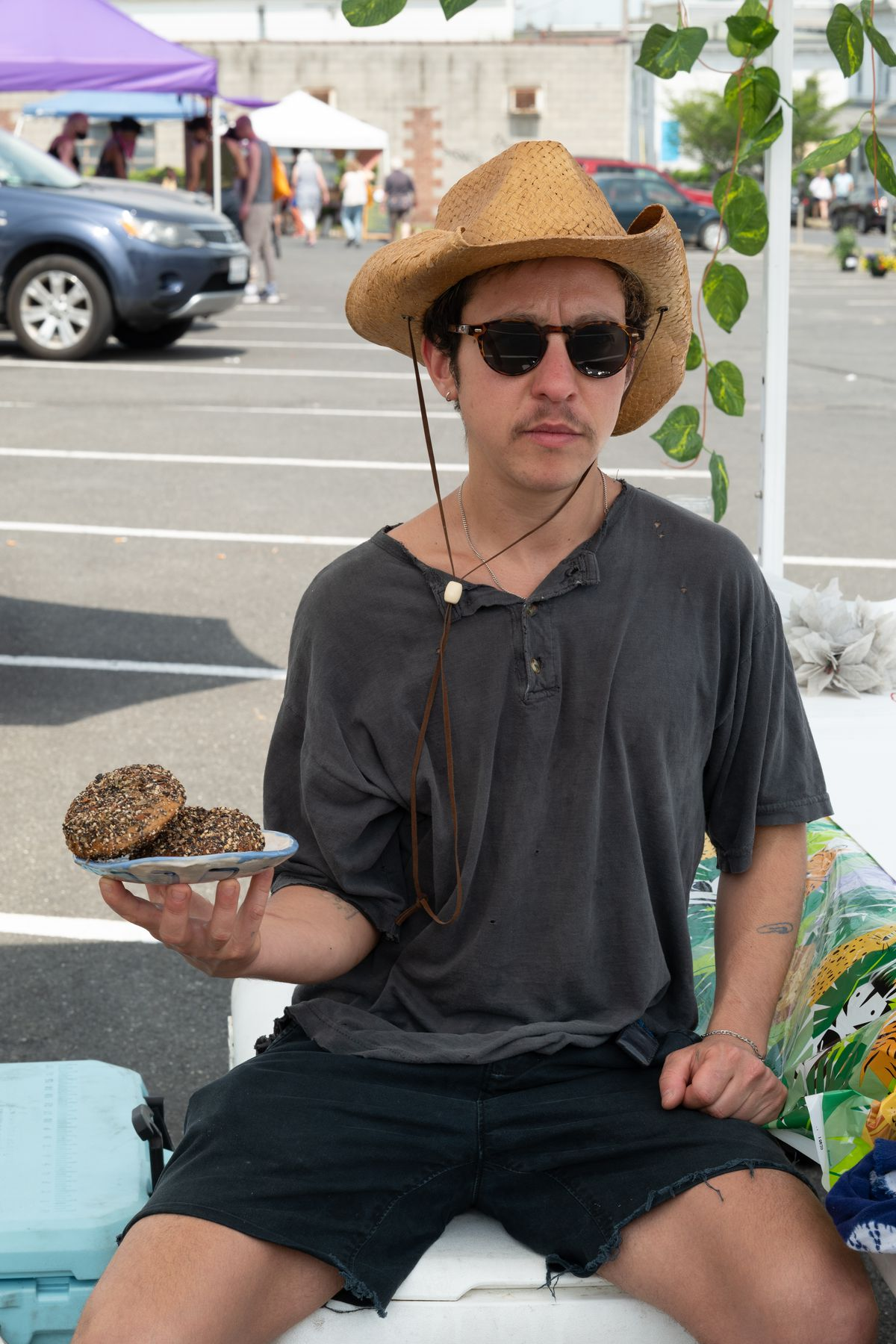 Tray Tepper sits on a cooler, holding a plate of homemade bagels.