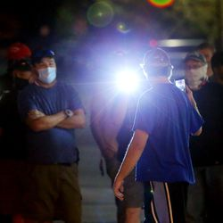 Counterprotesters shine high-powered flashlights at a man taking video of them during a demonstration at the West Valley City Police Department on Wednesday, Sept. 16, 2020.